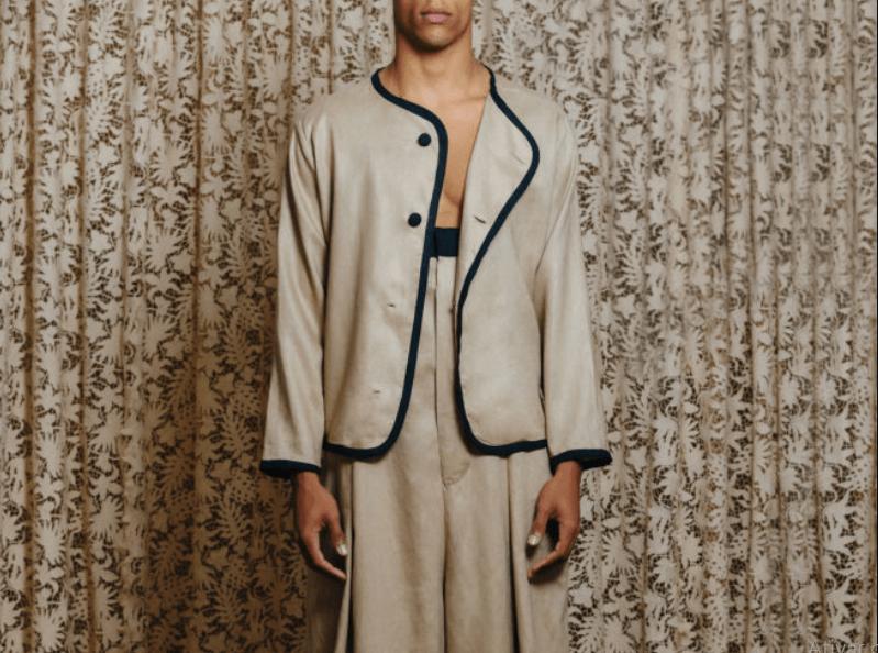 Modelo usa casaco e calça em tom neutro com punho, cós e botões pretos.