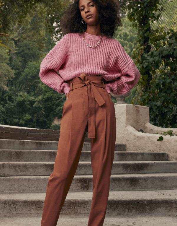 Modelo veste blusa de rosa e calça alfaiataria