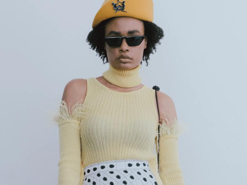 Modelo veste regata de tricô amarela, boina, gola e mangas soltas