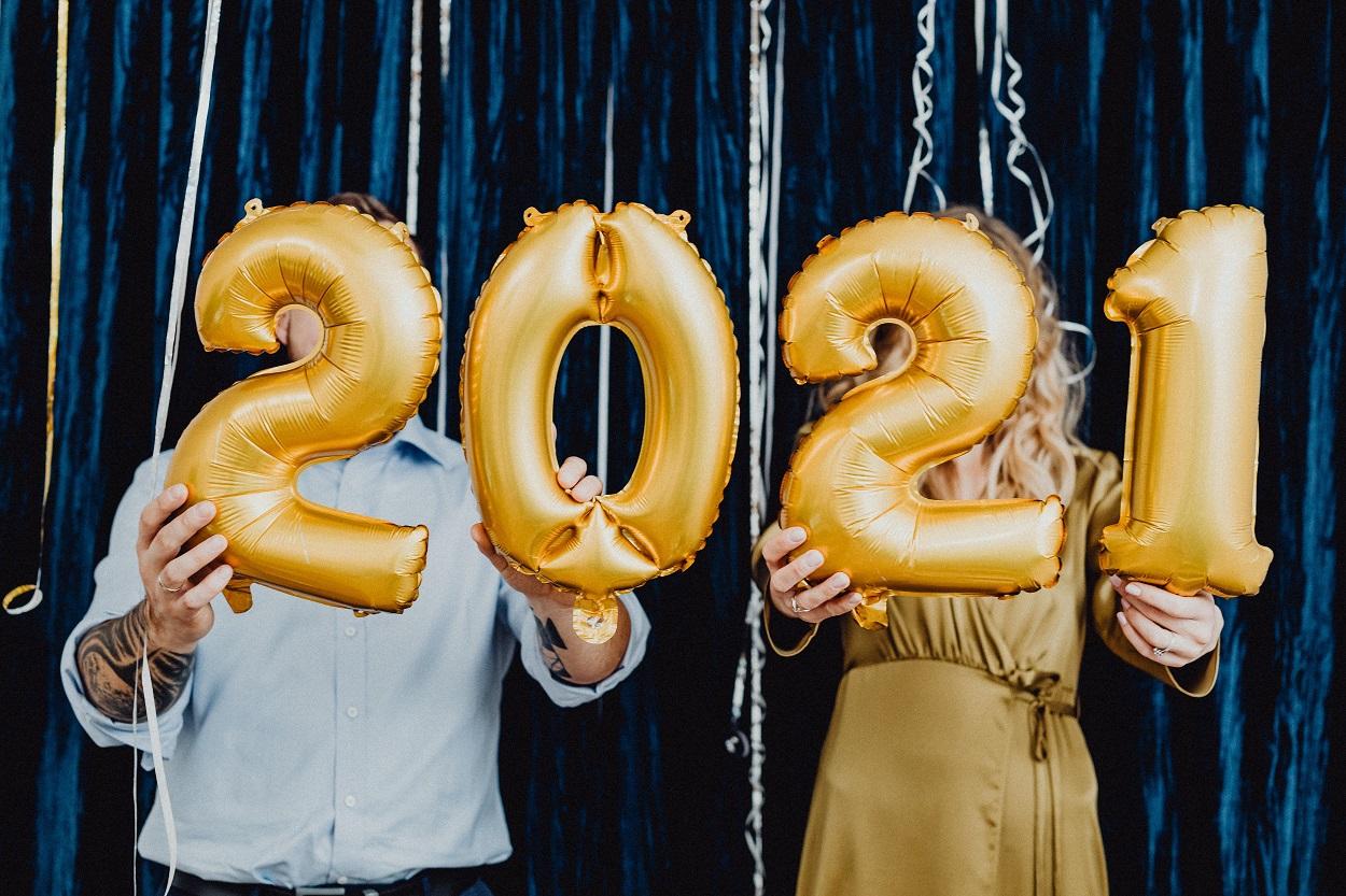 duas pessoas segurando balões de números 2021