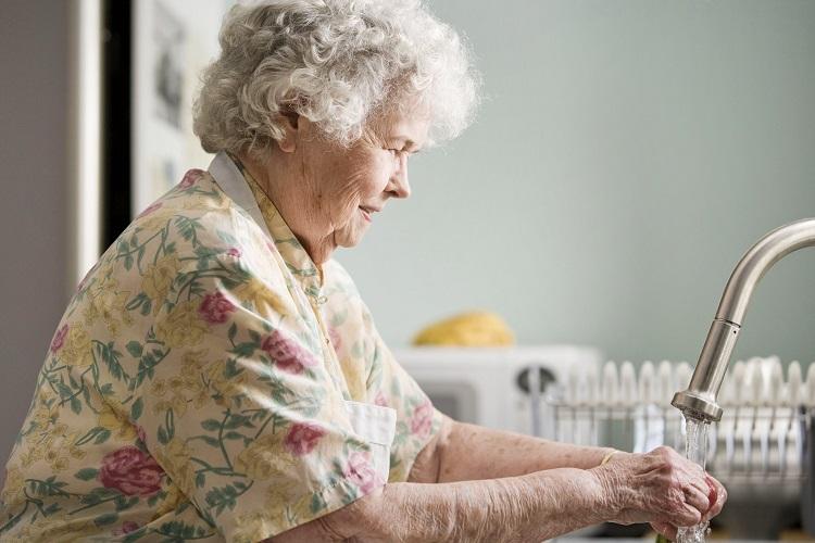 mulher idosa lavando as mãos
