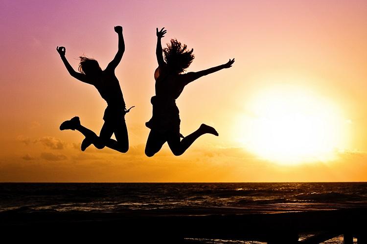 duas silhuetas de mulheres pulando com pôr do sol ao fundo