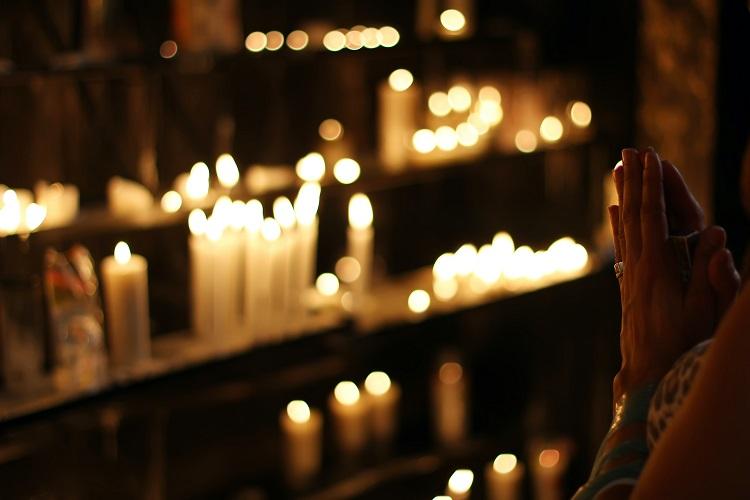mulher fazendo orações de Ano Novo em frente a velas acesas