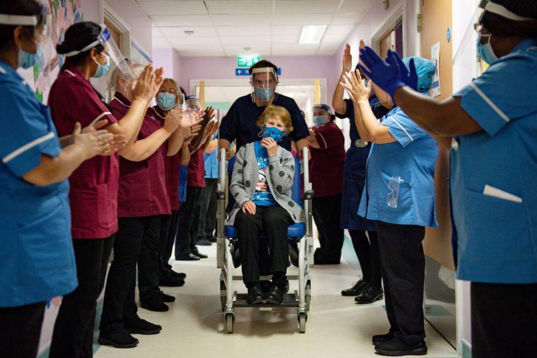 Mulher de 90 anos é aplaudida por profissionais após ser a primeira mulher a tomar a vacina contra a Covid-19.