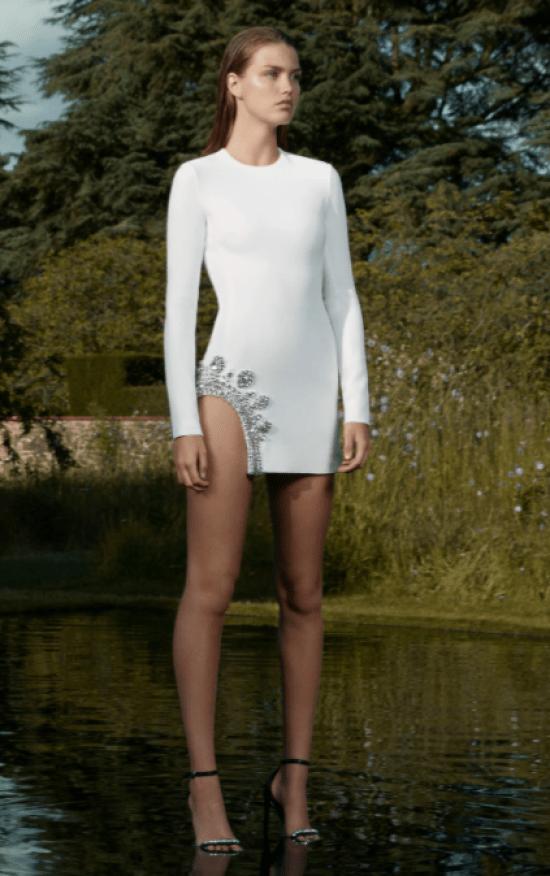 Vestido curto branco, manga comprida e fenda lateral com pedraria