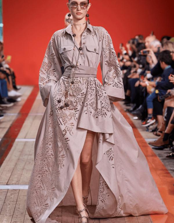 Modelo usa vestido laise com fenda e manga comprida