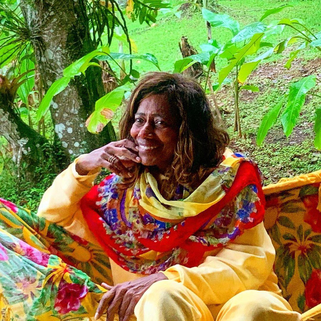 Glória Maria sentada em rede colorida.