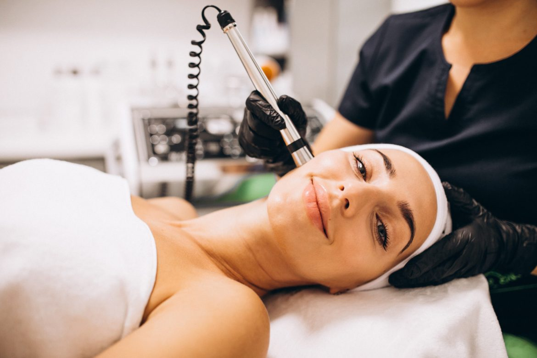 mulher deitada em maca fazendo tratamento de laser para manchas na pele