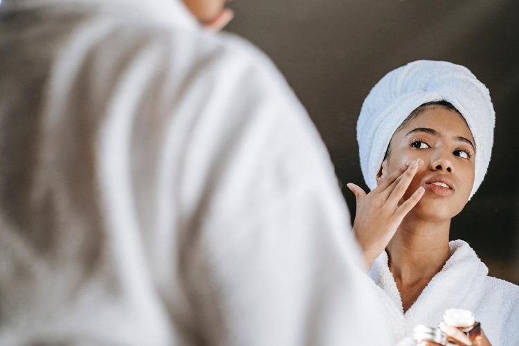 mulher no espelho aplicando creme de clareamento de manchas na pele