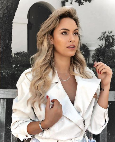 Sarah Andrade está vestida com um casaco elegante na cor branca.