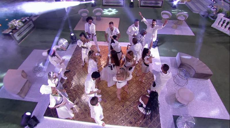 Na foto, aparecem os participantes na pista de dança em uma festa do BBB 21. Eles estão vestidos de branco.