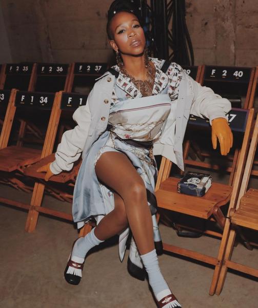 Na imagem, aparece a cantora Karol Conká sentada em uma cadeira de madeira vestindo uma roupa estilosa com cores claras.