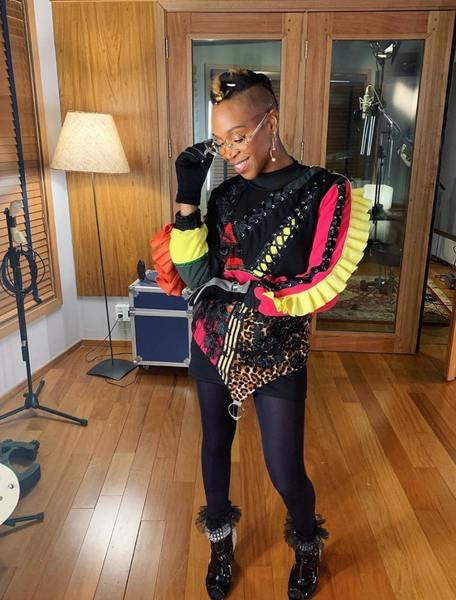 Na foto, aparece a cantora Karol Conká posando para foto. Ela está vestida de preto de forma estilosa e segura seu óculos.