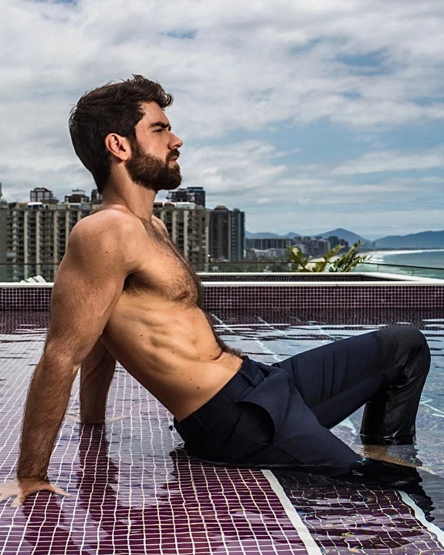 Ator Marcos Pitombo na piscina, usando calça.