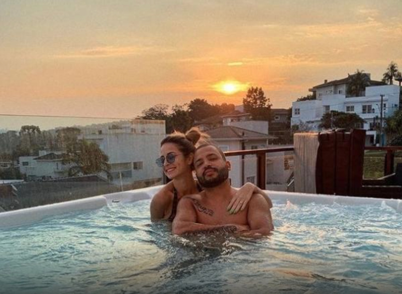 Na foto, aparece Projota e esposa em piscina