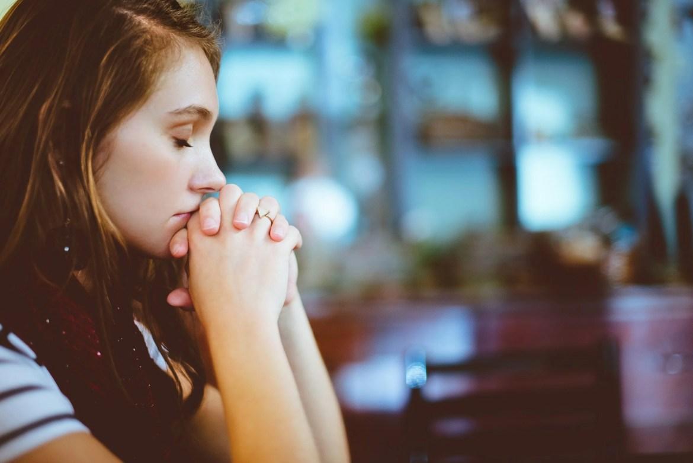 Mulher com os dedos entrelaçados em posição de oração