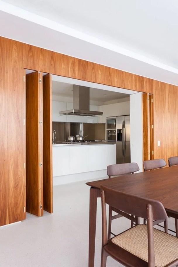 Cozinha escondida com porta sanfonada