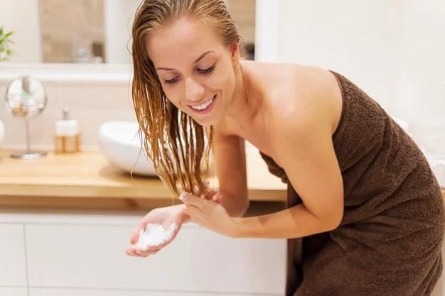 mulher lavando o cabelo com hidratante