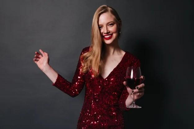 mulher com vestido de gala vermelho segurando uma taça