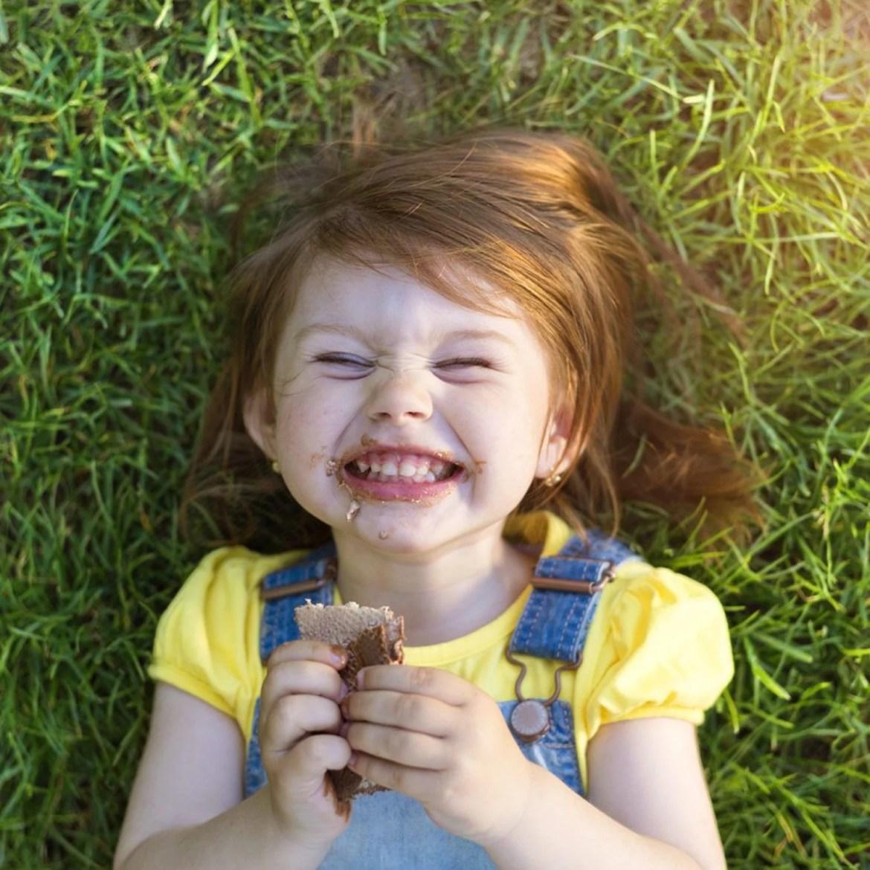 Garotinha comendo chocolate.