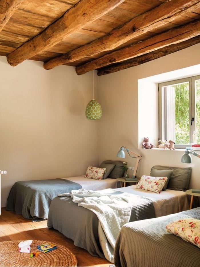 Quarto com três camas e teto de madeira