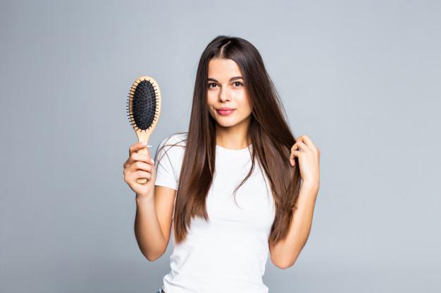mulher com escova de cabelo