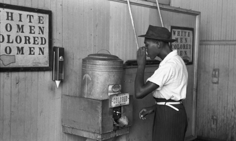 Homem a beber água no depósito próprio para os homens negros (Colored Men).
