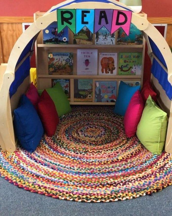 Cantinho da leitura com almofadas e tapete.