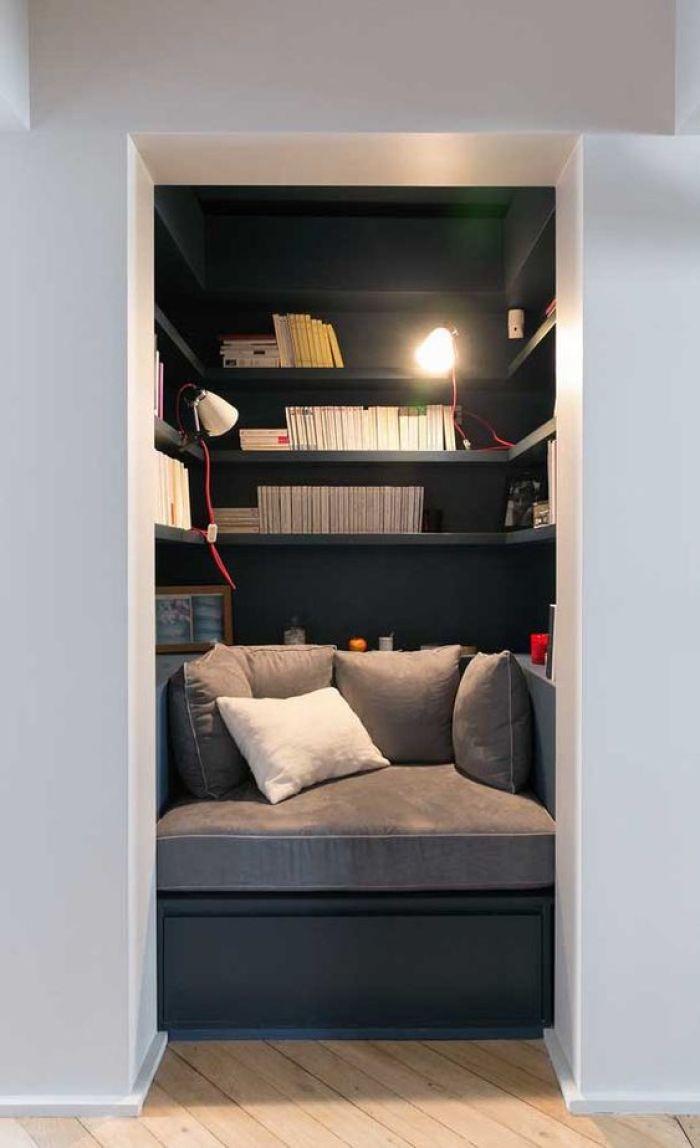 Cômodo pequeno com livros e sofá.