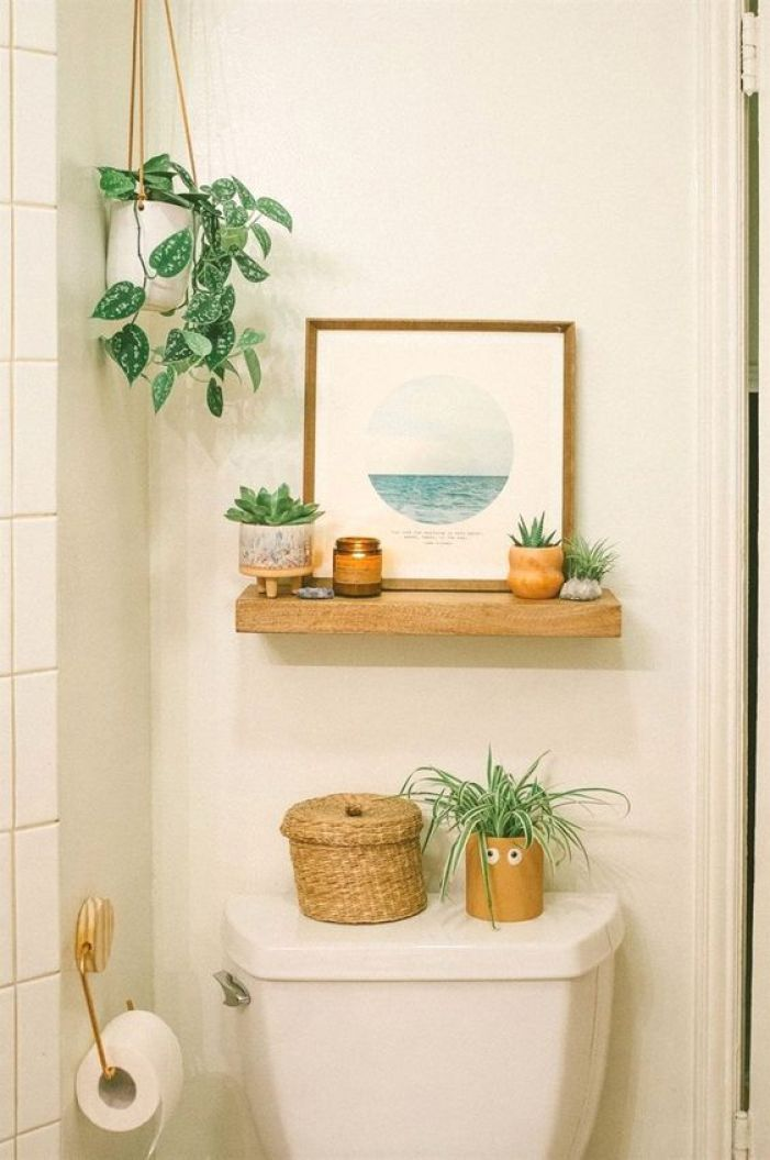 Banheiro decorado com plantas e quadro.