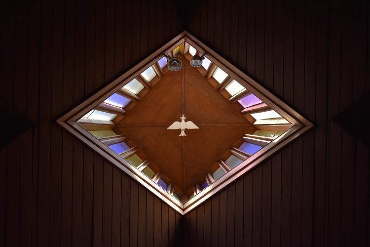 teto de igreja com vitral de pomba branca