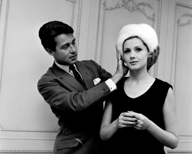 Roy Halston a ajeitar um chapéu em uma modelo, em um salão da Bergdorf Goodman.