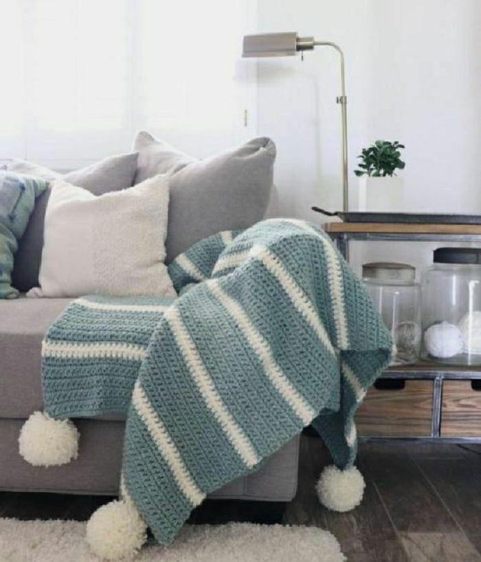 Sofá cinza com manta listrada.