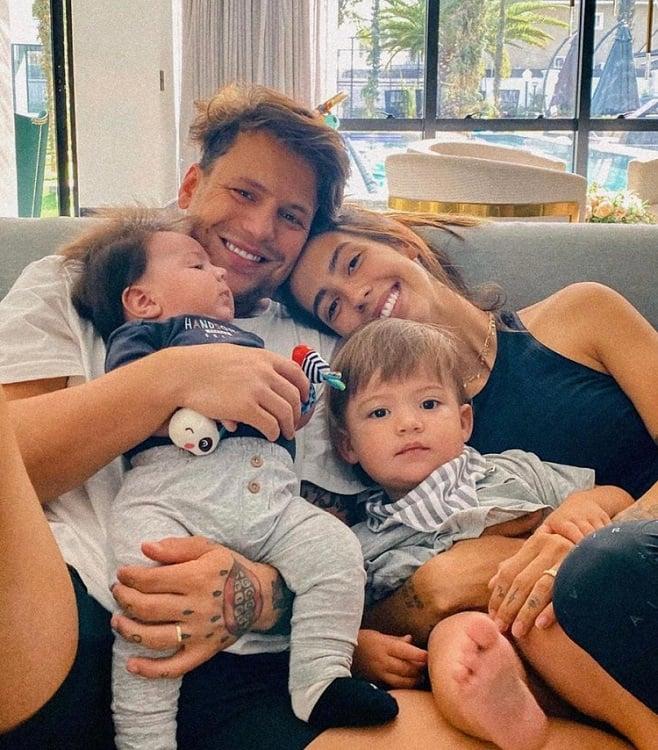 Saulo Pôncio e Gabi Brandt no sofá da sala com os filhos Davi e Henri