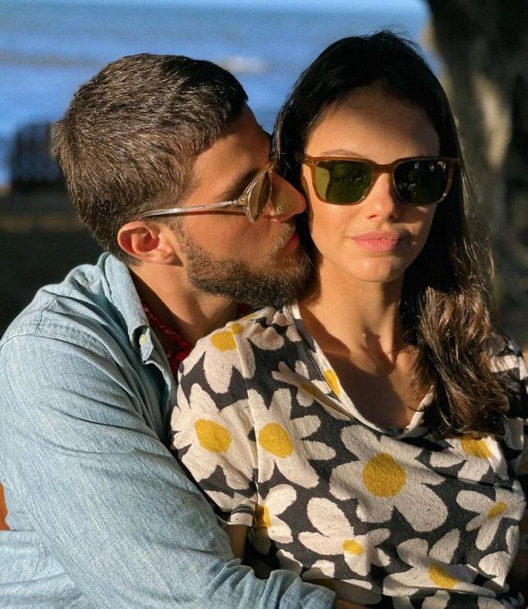 Ambos de óculos escuros, Chay Suede dá um beijo no rosto de Laura Neiva