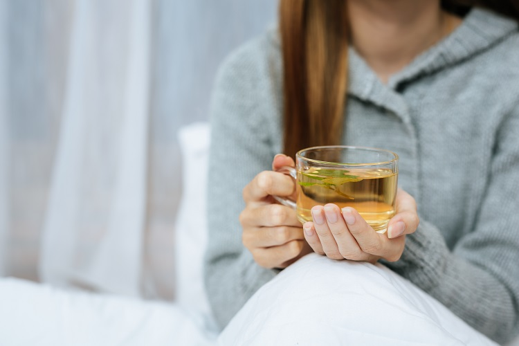 mulher segurando xícara transparente