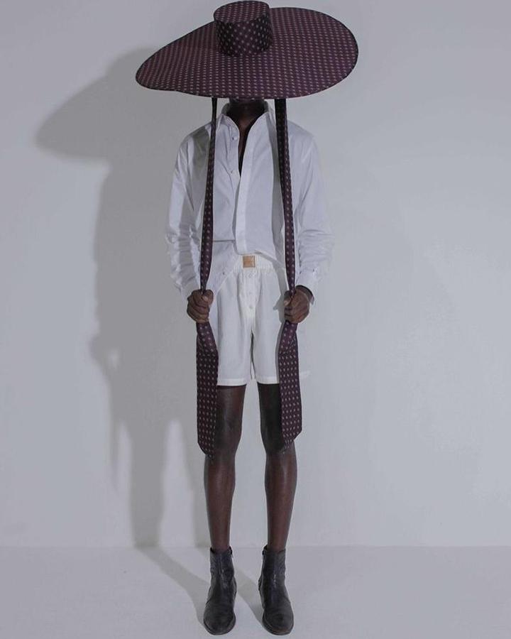 Modelo com blusa branca de botões e chapéu grande de cor escura.