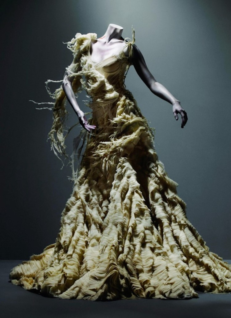 Manequim com vestido bege, com plumas, tecidos descontruídos