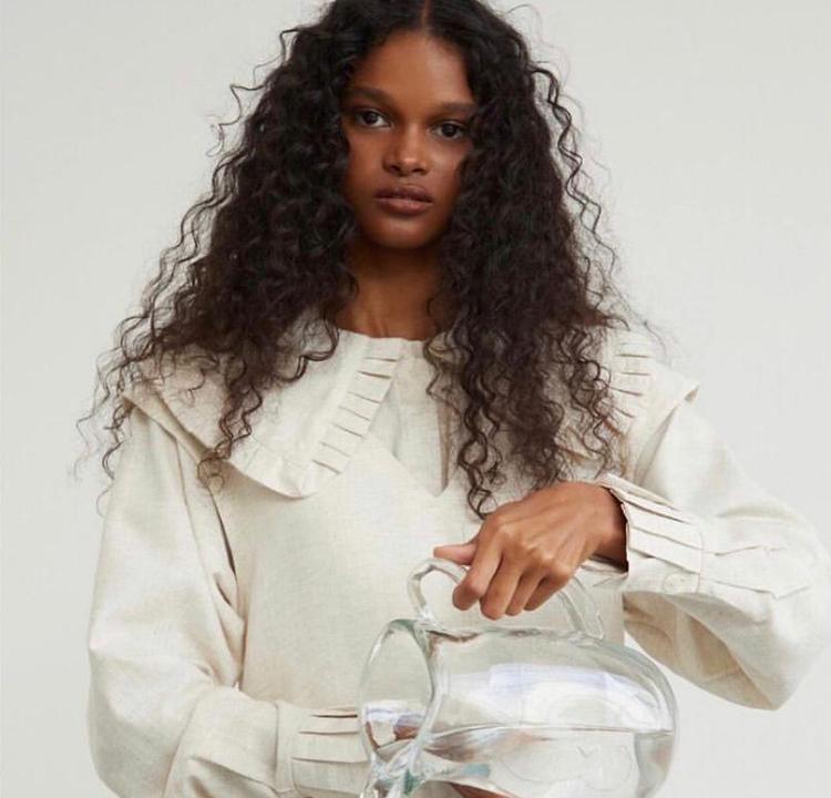 Modelo com blusa branca da Aluf.