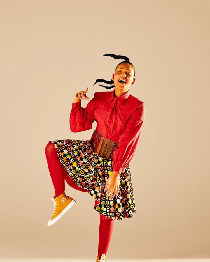 Modelo com blusa de mangas vermelha, meia calça vermelha, tênis amarelo e saia colorida.