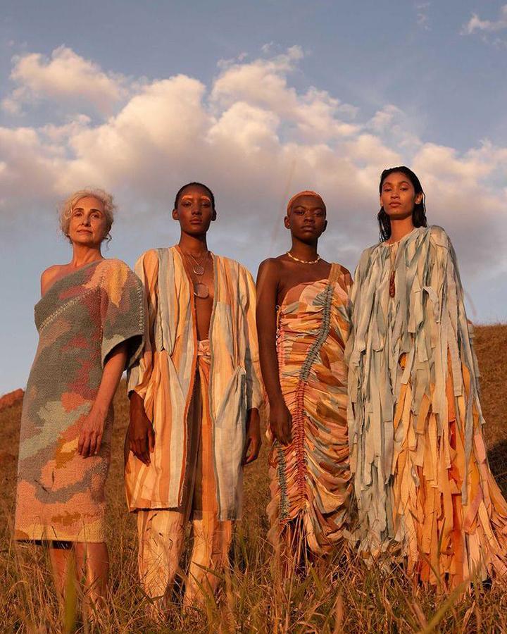 Quatro modelos estão usando roupas coloridas lado a lado.