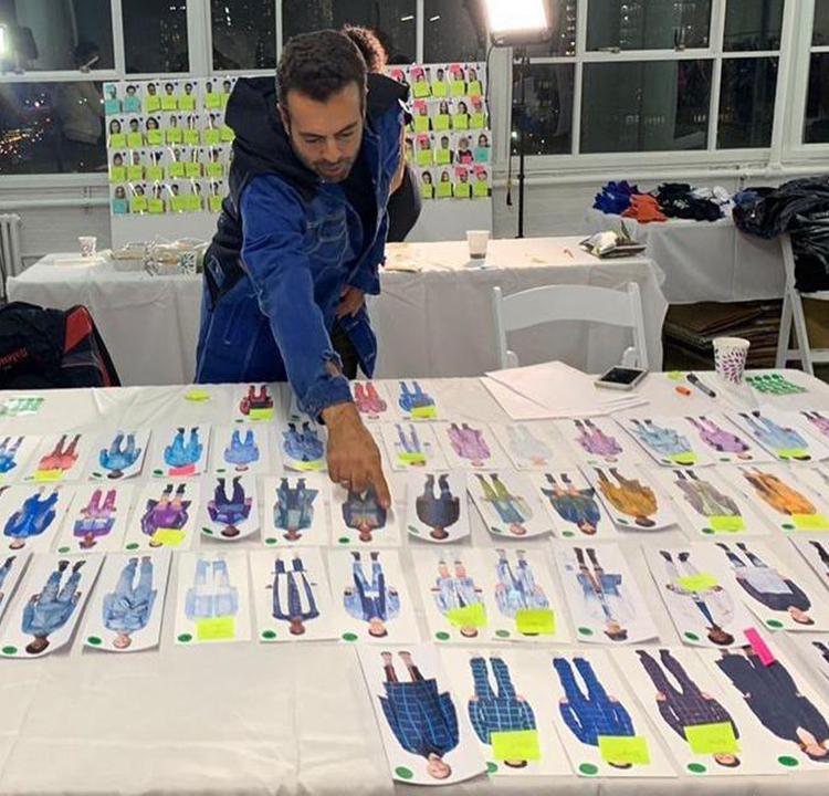 João Foltran atrás de uma grande mesa cheia de desenhos de combinações de roupas. Ele aponta para um desenho no centro da mesa.