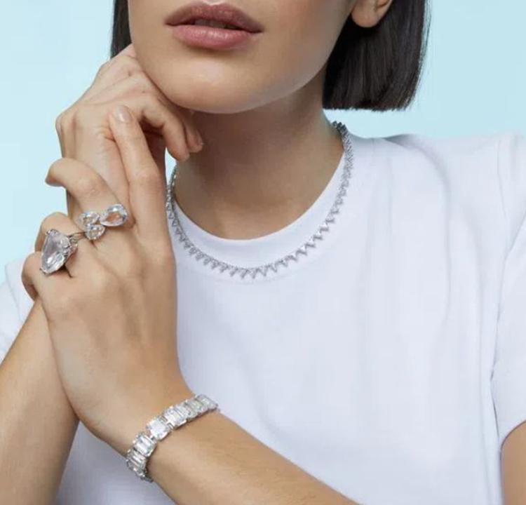Foto de uma mulher usando dois aneis e uma pulseira de cristais brancos.