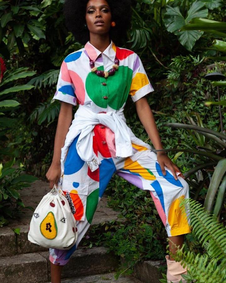 Modelo com macacão branco com bolotas coloridas.