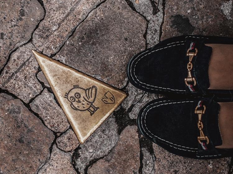 Foto do pé de uma pessoa usando calçado mocassins com fivela, tendência do inverno em 2021.