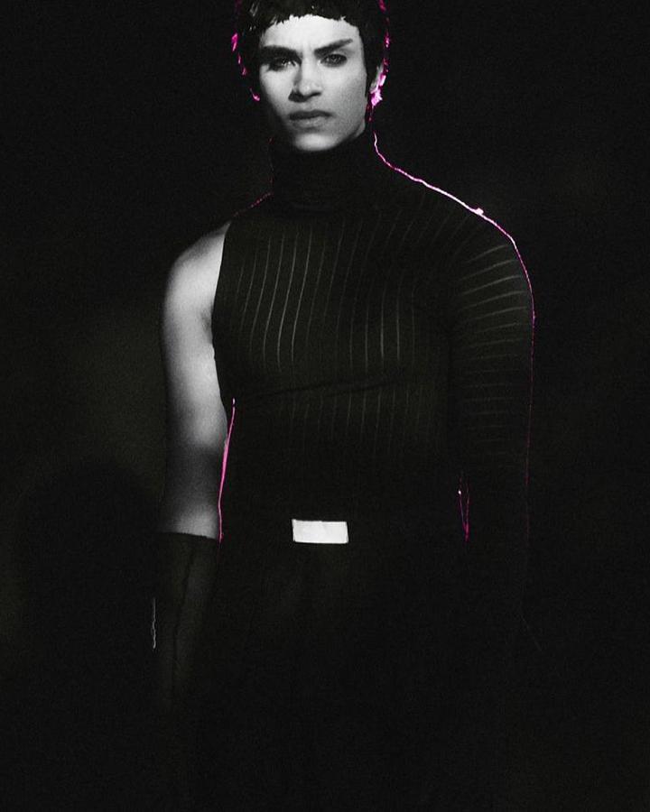 Modelo com uma blusa preta com só uma manga.