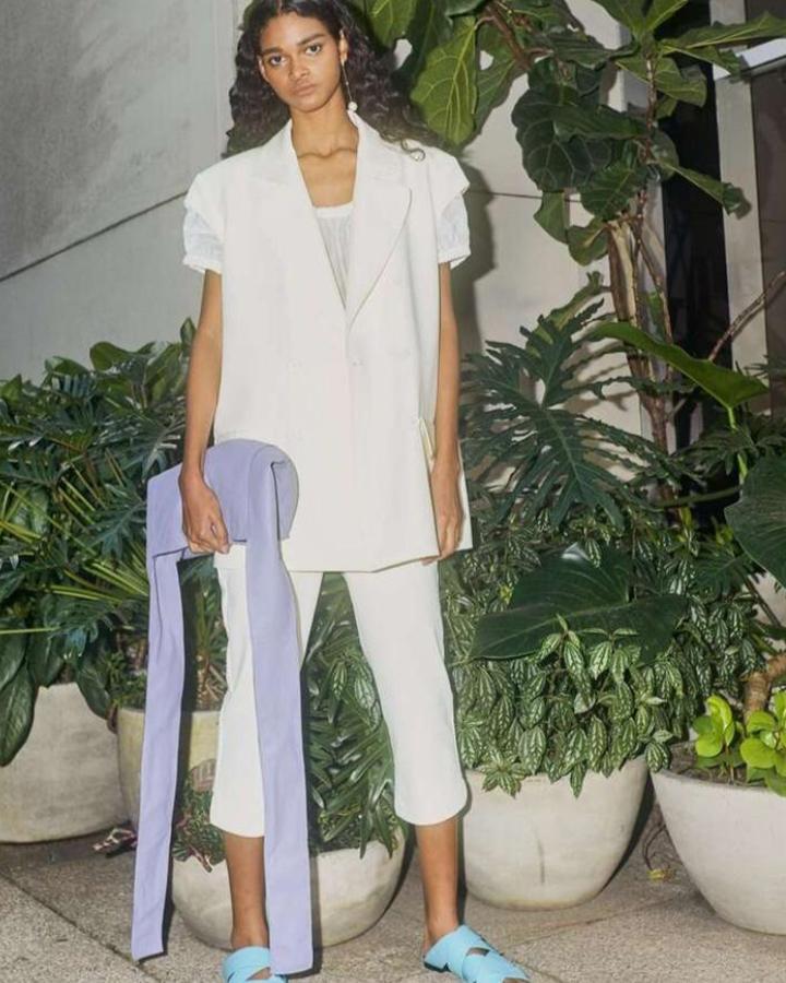 Modelo com terno de verão branco e bolsa roxa.