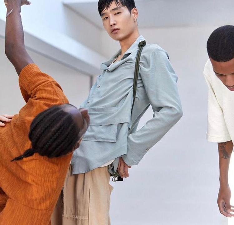 Três modelos, um usando uma blusa laranja, um usando uma blusa azul de botão e uma calça bege, o outro está quase fora do enquadramento da foto.