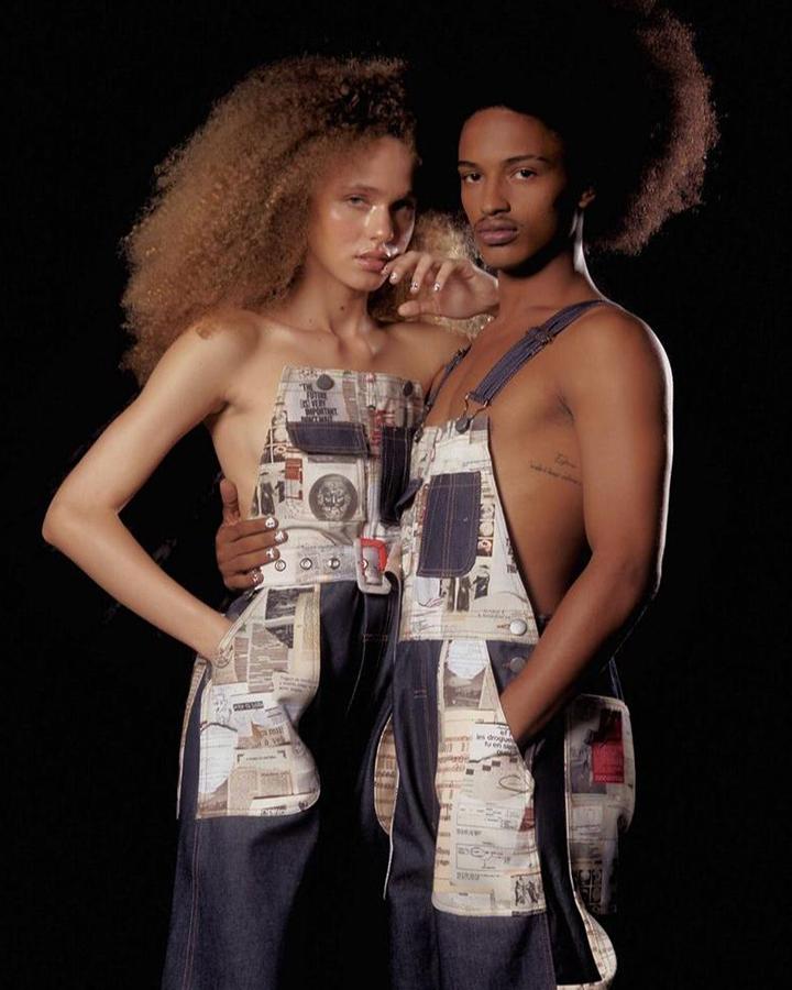 Um casal de modelos usam um macacão jeans com detalhes coloridos.