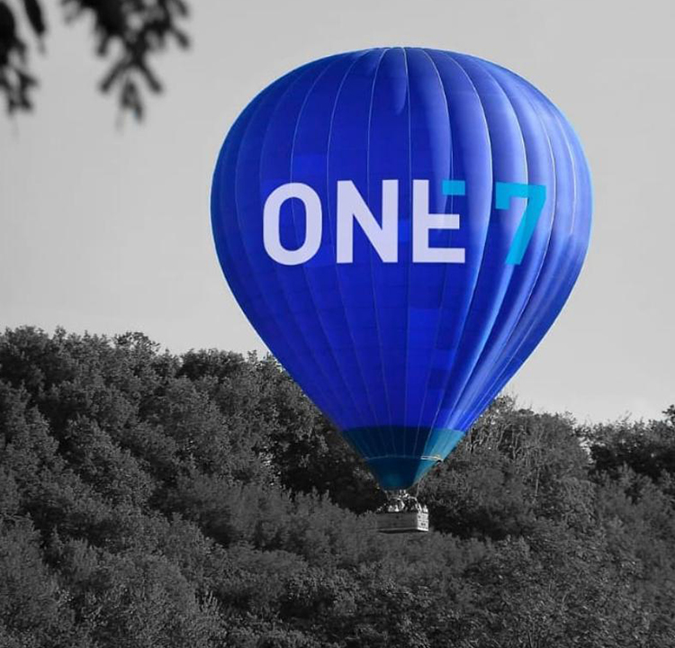 Fundo da imagem é uma floresta em preto e branco. Um balão azul com One7 escrito está no centro da foto.